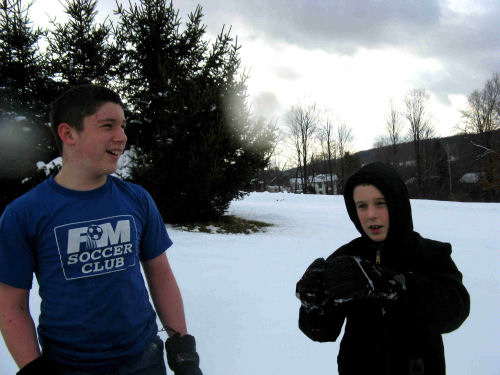 Justin and Owen imagining rolling snow boulders on the hill across the road